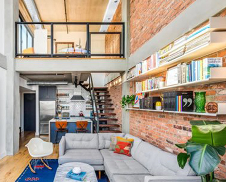 Interior of what seems to be a studio apartment with the interior walls built with Antique Warehouse Red Brick Veneer. There's a book shelf to the right, stairs in the back and furniture on the lower level.