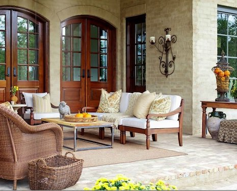 Patio and walls built with Old Chicago Brick Floor Tile. The patio has furniture like patio chairs, coffee table, cushions and lamps on the house walls.