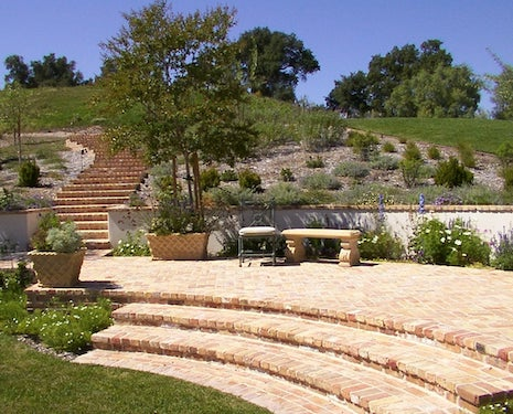 Auditorium style area with stairs coming down from a hill towards an open area that leads to the center after going down three stairs built with Old Chicago Pavers.