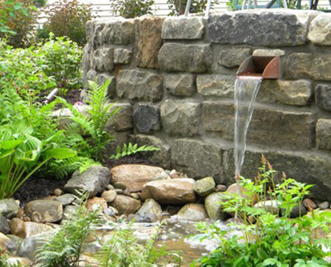 Fountain type of structure built with Reclaimed Reservoir Stone. There are rounded rocks and plants where the water falls.